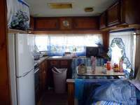 The kitchen: refrigerator, table, microwave oven, stove, sink, dishes